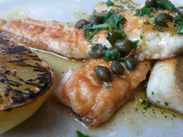 whole plaice with lemon wedge